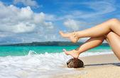 Fotografie Womens legs on a beach