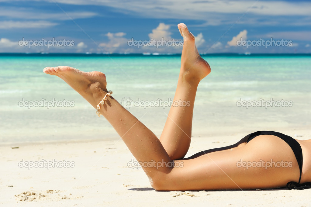 Women's legs on a beach