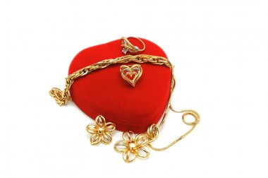 Red heart-shaped box and gold jewelery on white