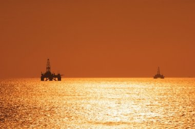 Two offshore oil rigs during sunset in Caspian se