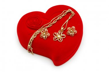 Golden earrings and chain on red heart-shaped box