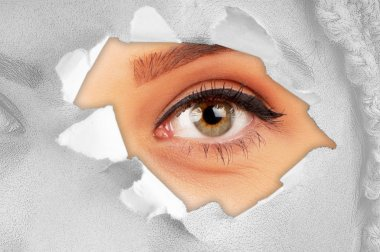 Woman eye through hole in paper stock vector