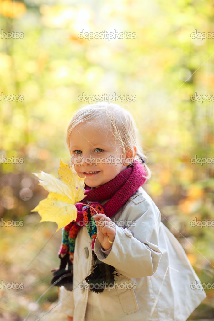 Toddler girl holding yellow leaf