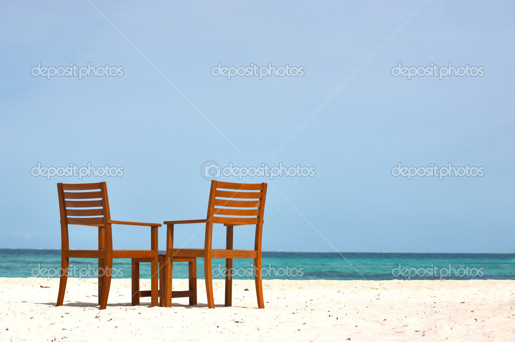 Couple of chair with the table on the shore. Plenty of sky space for the text