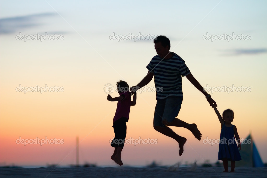 Father and kids jumping at sunset