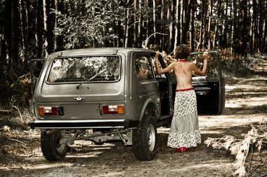 Vintage topless girl posing at the car