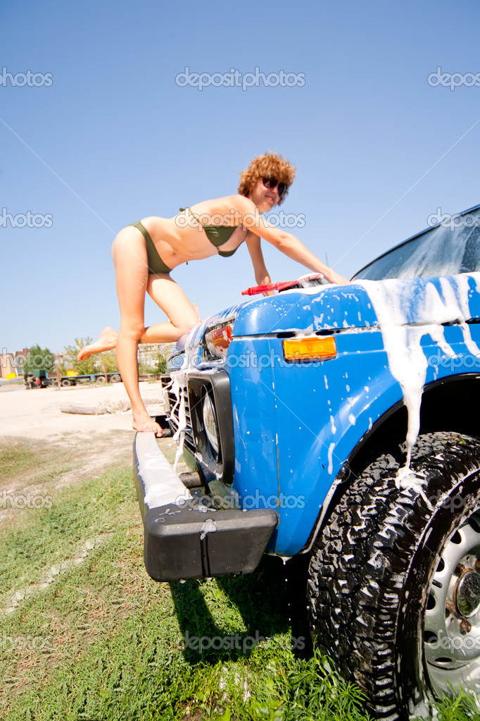 Girl in bikini washing car with selective focus
