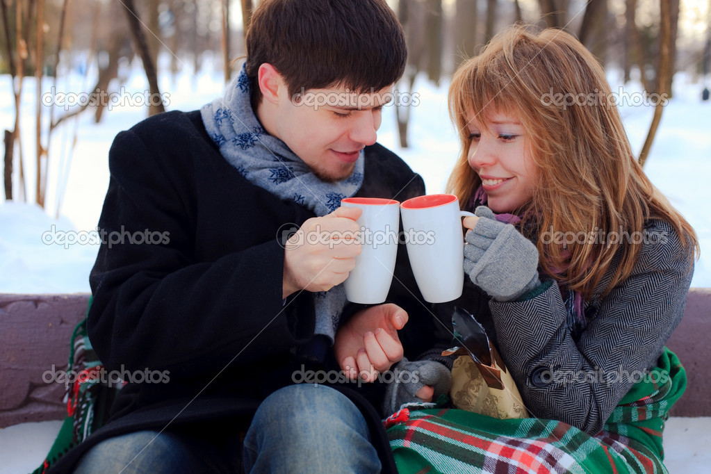 Young beloved couple warming themselves in the winter park
