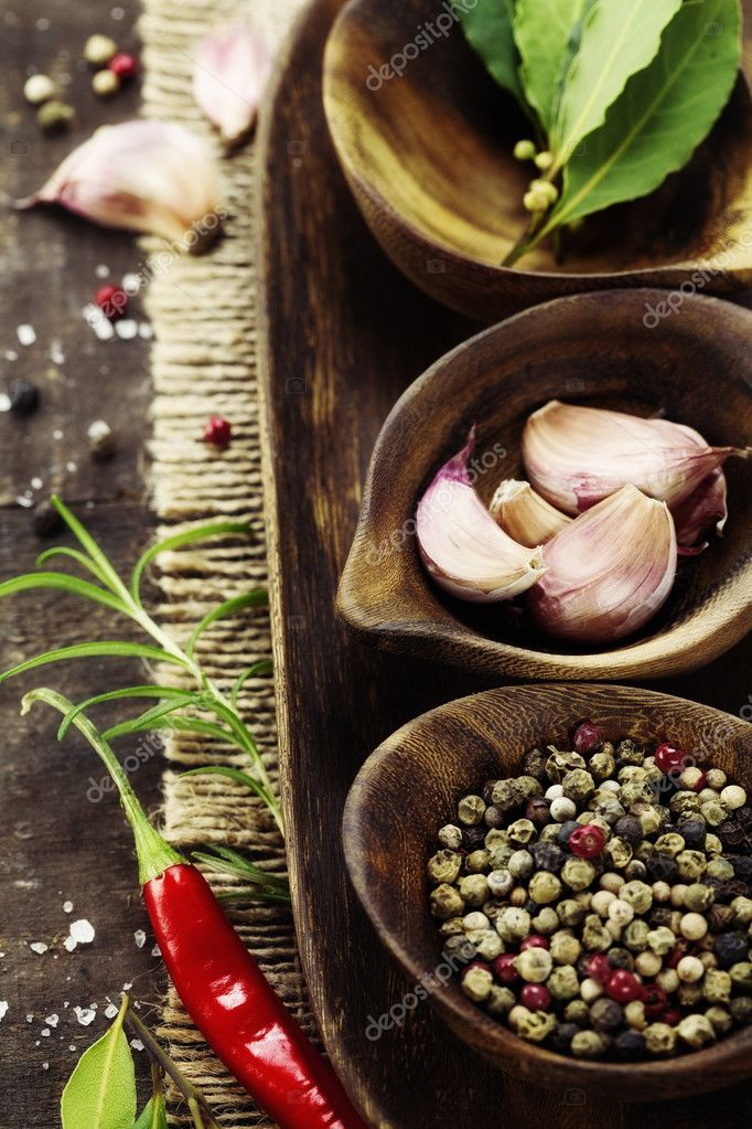 Wooden bowls with fresh herbs and spices