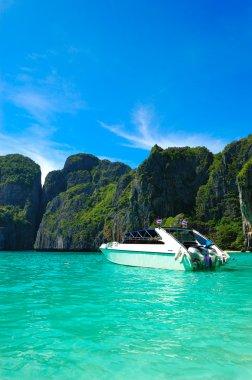 Motor boat on turquoise water of Maya Bay lagoon, Phi Phi island