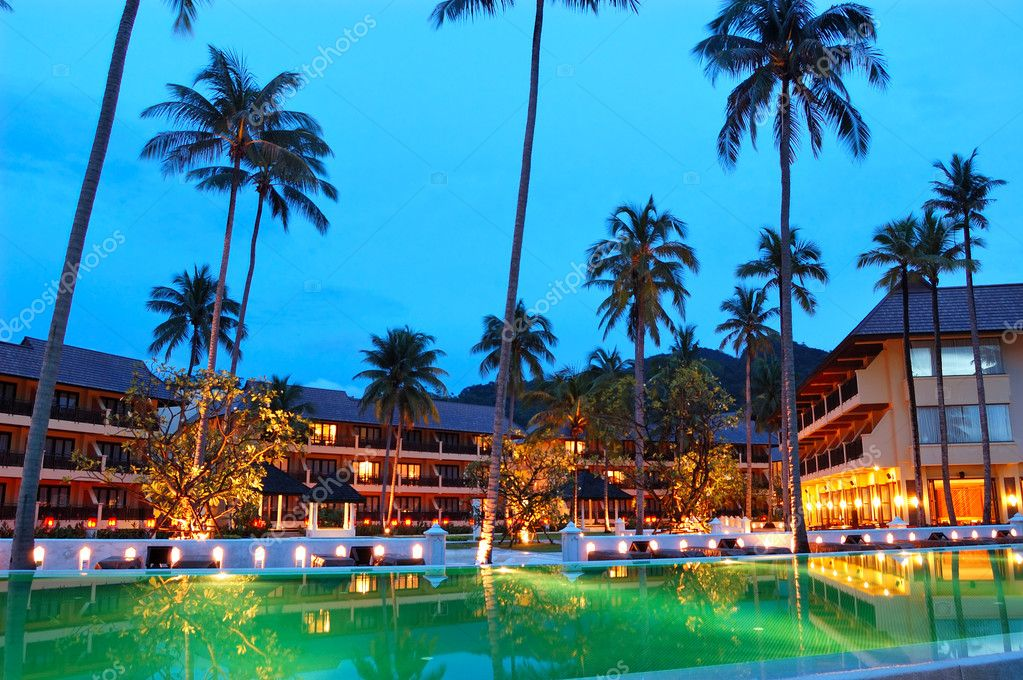 Green swimming pool near open-air restaurant in night illuminati