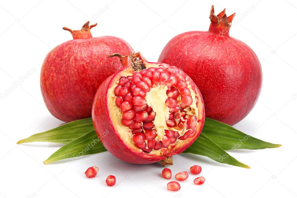 Pomegranate fruits with green leaf and cuts isolated