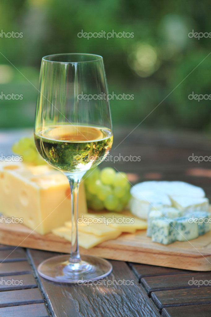 Various sorts of cheese, grapes and white wine