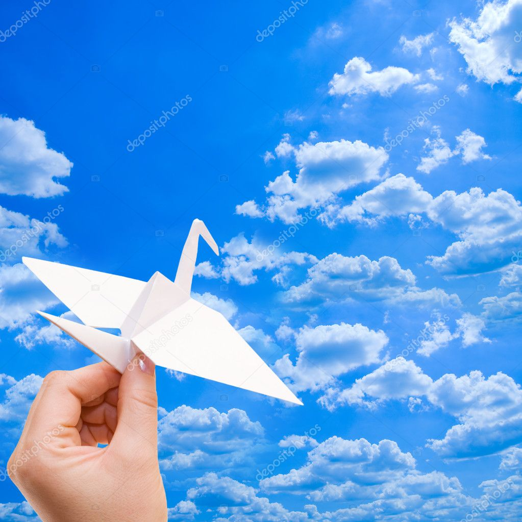 Paper crane against the blue sky