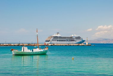A small fishing boat and large cruise ship in the Mediterranean near the is