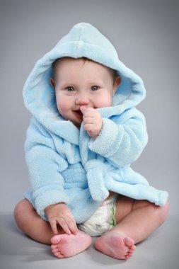 Charming baby in a blue bathrobe