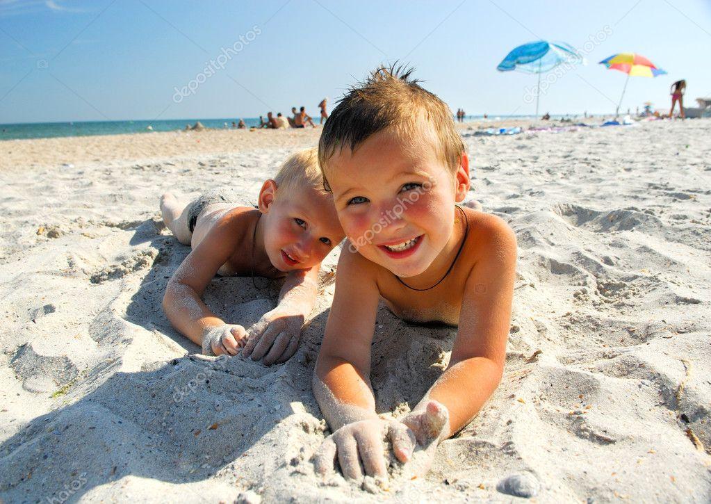 lachende jongens liggend op een strand — Stockfoto