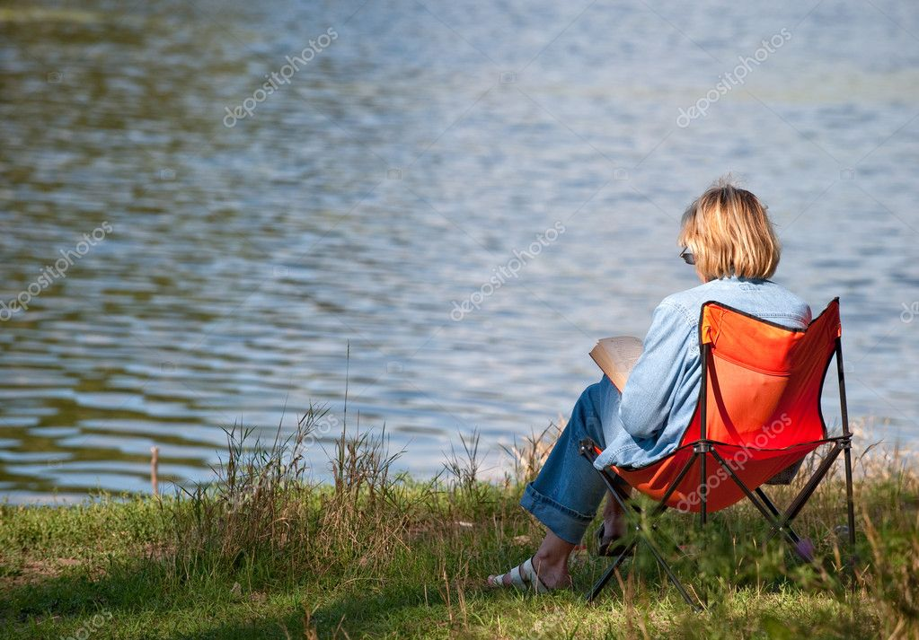 The woman reading the book on coast of lake