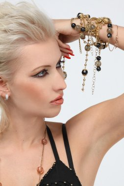 Fashion portrait of professional model with gold jewelry