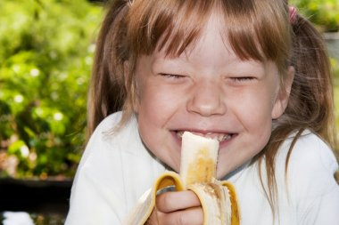 Little girl in the outdoors eats a banana and laughs