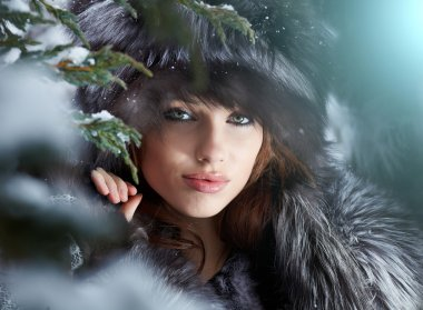 Beautiful young woman in winter forest