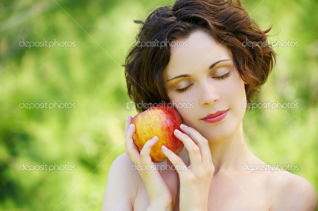 Outside portrait of beautiful young curly woman with eyes shut with red apple in park