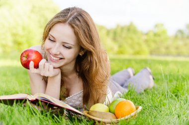 Charming girl with apples lies on green grass and reads book. stock vector
