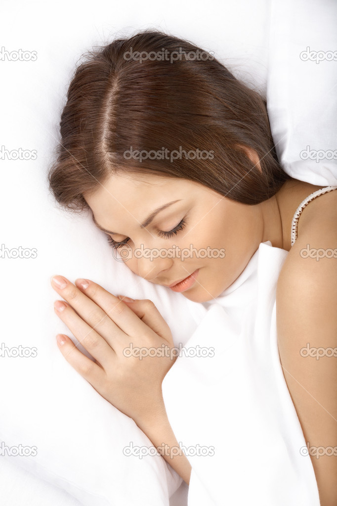 Close up of the beautiful girl sleeping in white bed