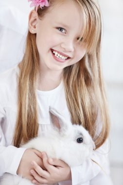 The little girl holding a white rabbit stock vector