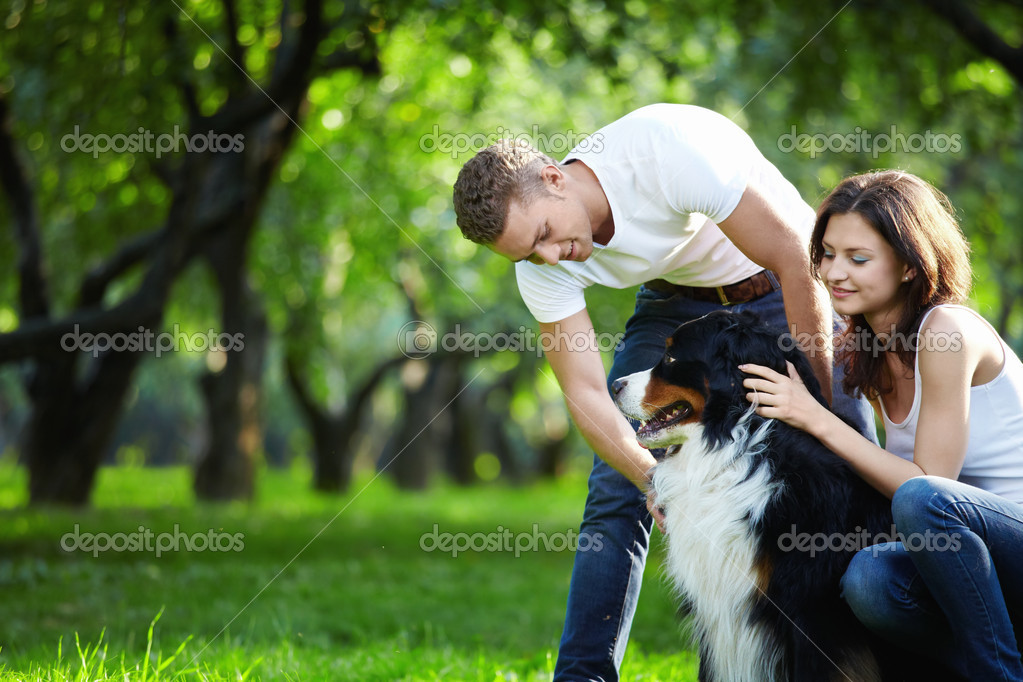 A young couple walking a dog