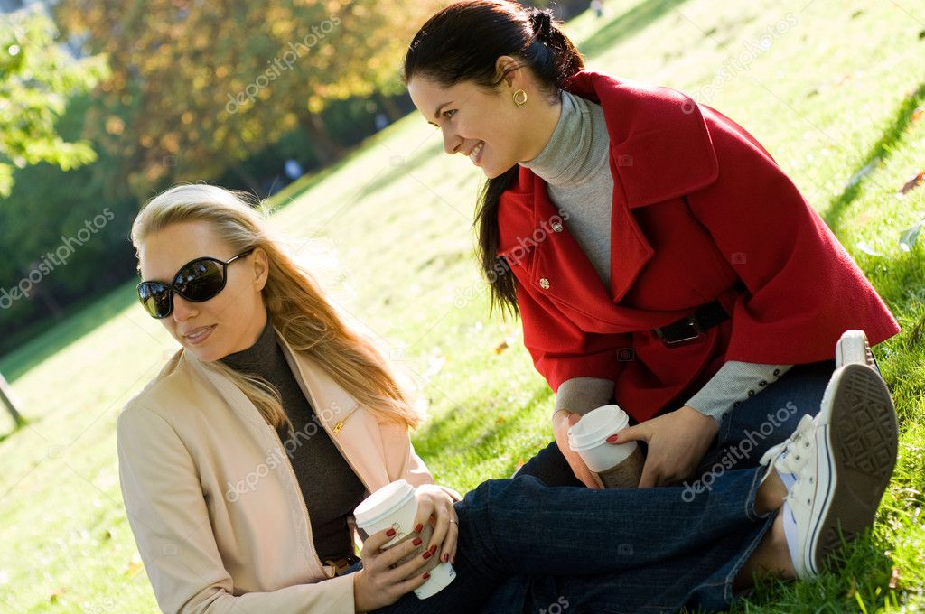 Two young women having coffee break together in park
