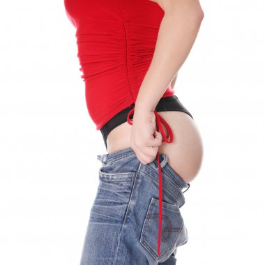 Woman trying to get in to old jeans.