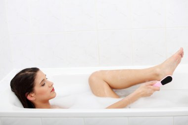 Woman in bath rubbing heel of foot