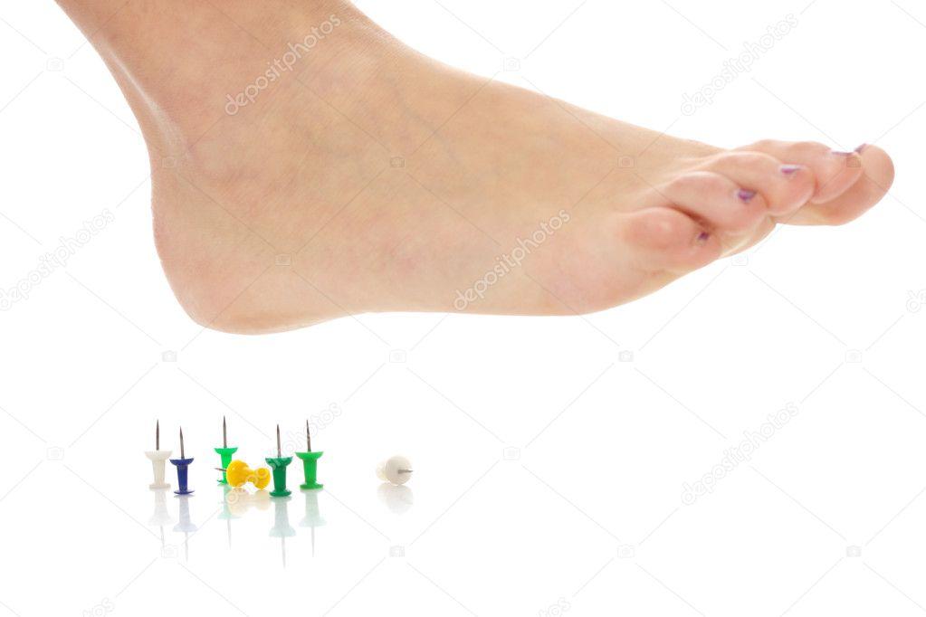 Female foot above pushpin