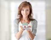 žena drží euro bankovky a model domu