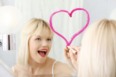 Young beautiful woman drawing big heart on mirror.