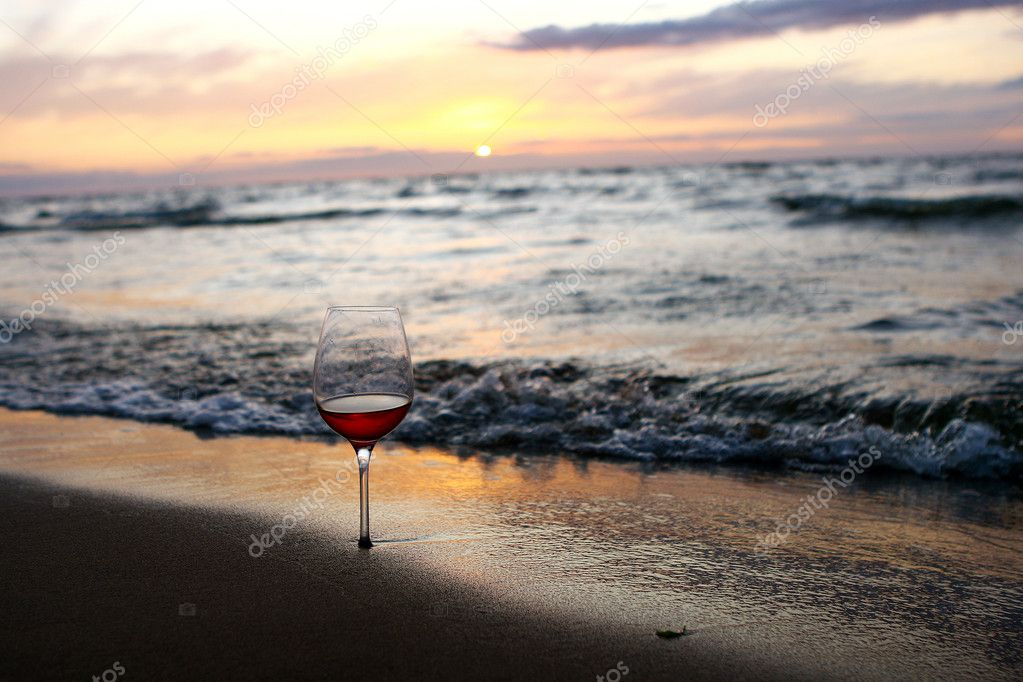 Alone glass of red wine on beach