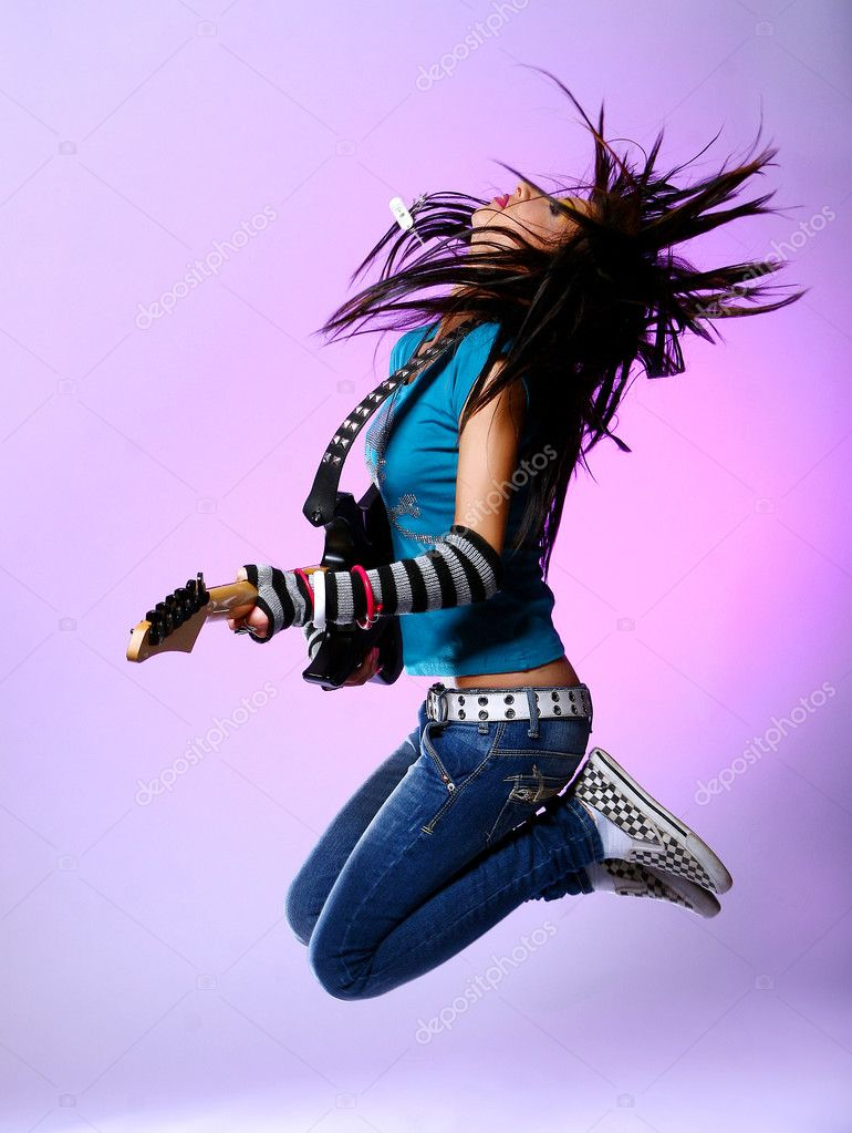 Young and beautiful girl jump with guitar