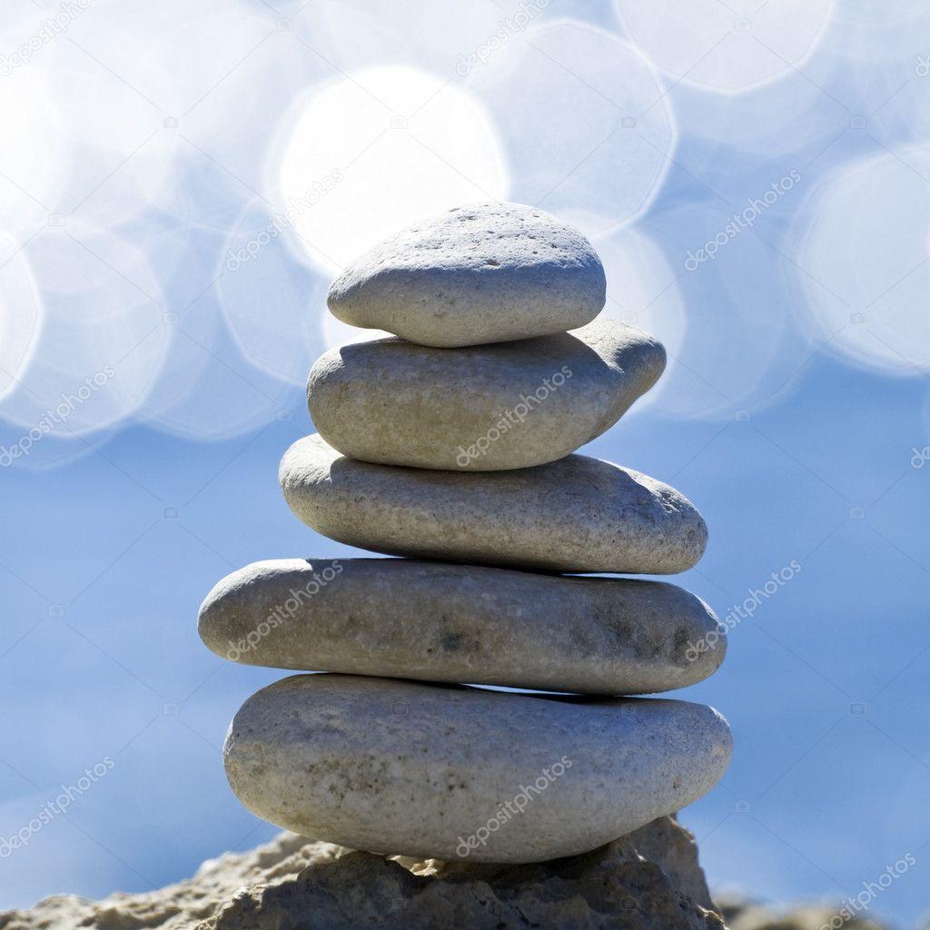 Pebbles stack over blurred sea