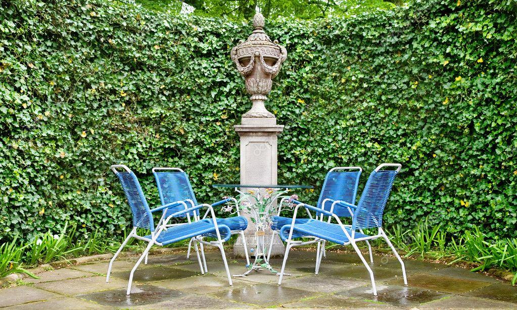 Chaises en osier et table en verre dans le jardin ...
