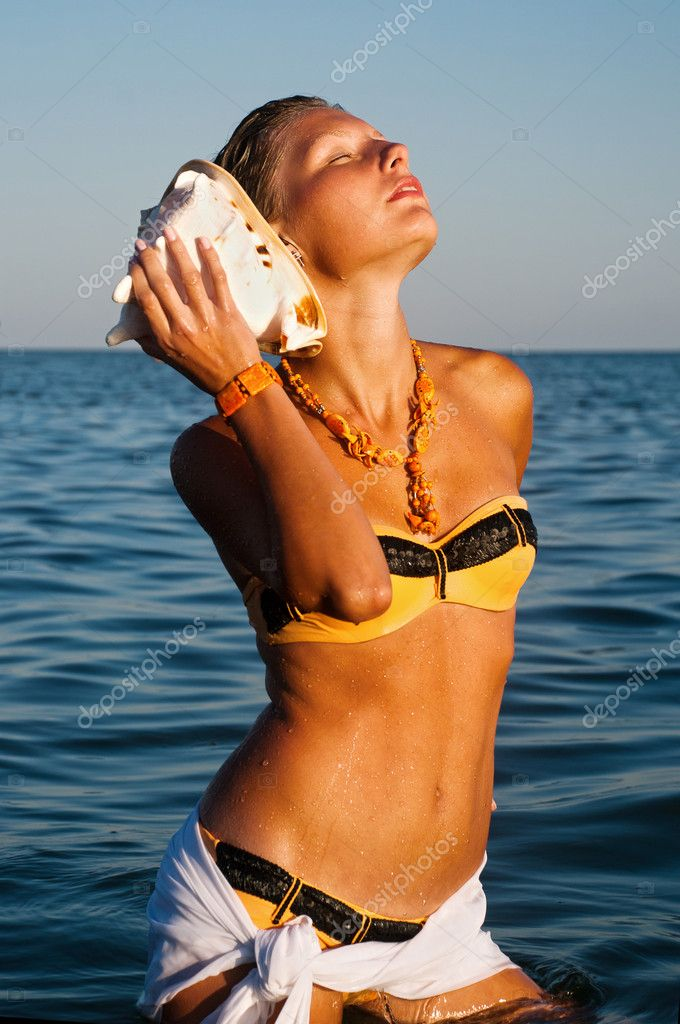 Portrait of a young gorgeous female listening seashell song