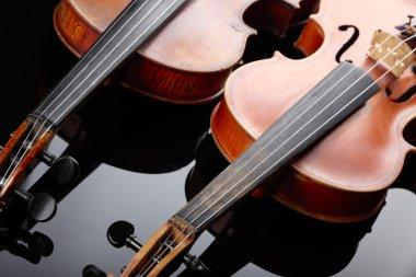 Two violins on dark background