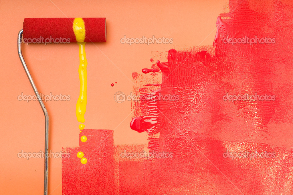 Paint roller with splash of yellow colors, painting with red color over a orange wall.
