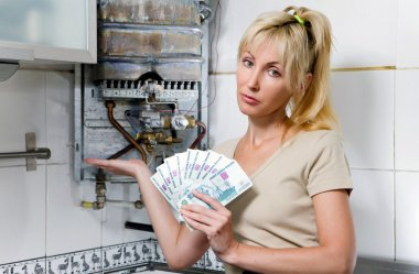 The sad woman the housewife counts up money for repair of a gas water heate