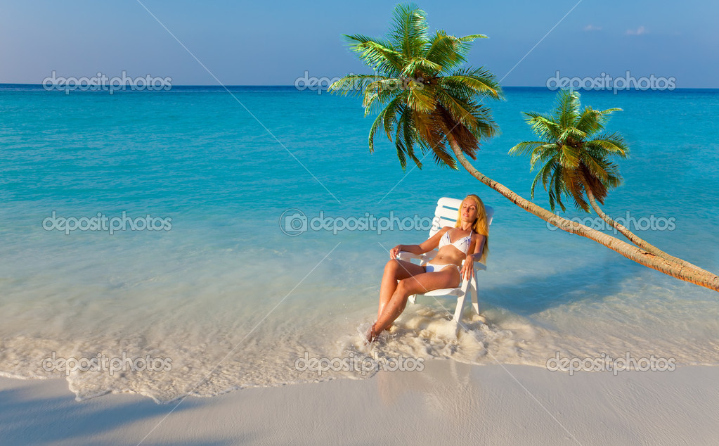 The girl in a chaise lounge at ocean under palm trees on a sunset