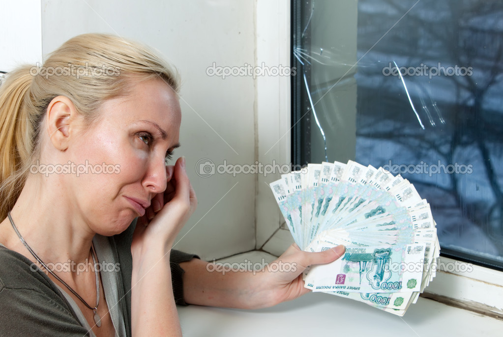 The housewife cries and counts money for repair of a double-glazed window w