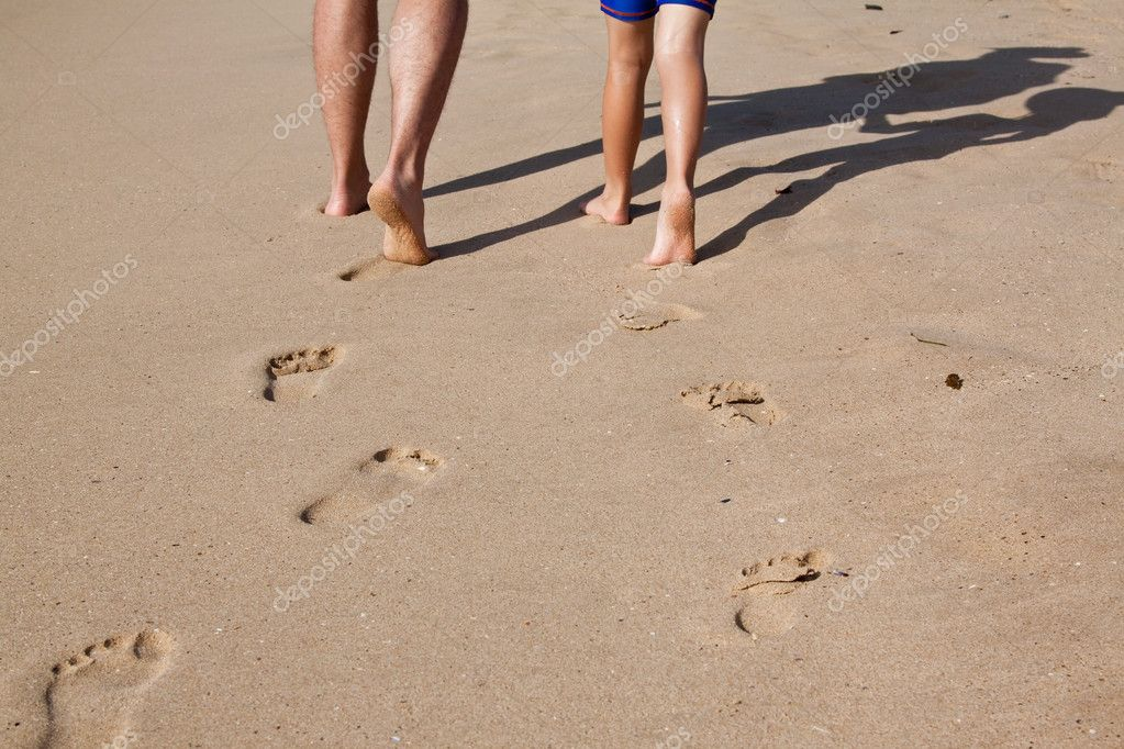 Footprints in wet sand of father and son