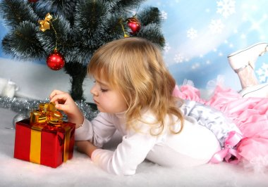 Beautiful girl with a gift lies near the Christmas tree