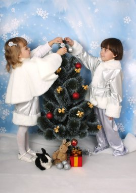 Boy and girl dressed as a silver dress decorate a Christmas tree