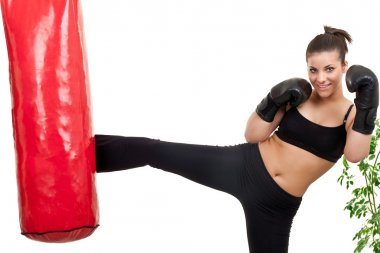 Female boxer kicking punching bag